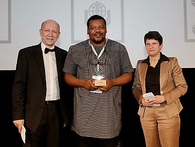 "Andreas Kuhlmann, Nnaemeka Ikegwuonu und Tanja Gönner stehen nebeneinande auf der Bühne bei der Preisverleihung des ""Start Up Energy Transition Awards"" an ColdHubs"